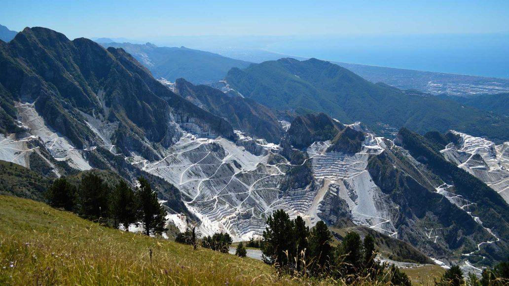Radreise Toskana: Diesen Traumblick werden Sie erleben. Blick auf die Marmorbrüche von Carrara und die Ligurische Küste. Ganz links am Meer liegt unser Hotel Versilia Palace