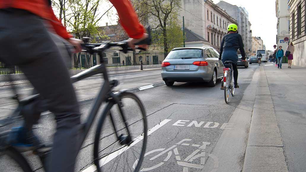 Fahrrad und Auto teilen sich nicht selten den Raum auf der Straße.