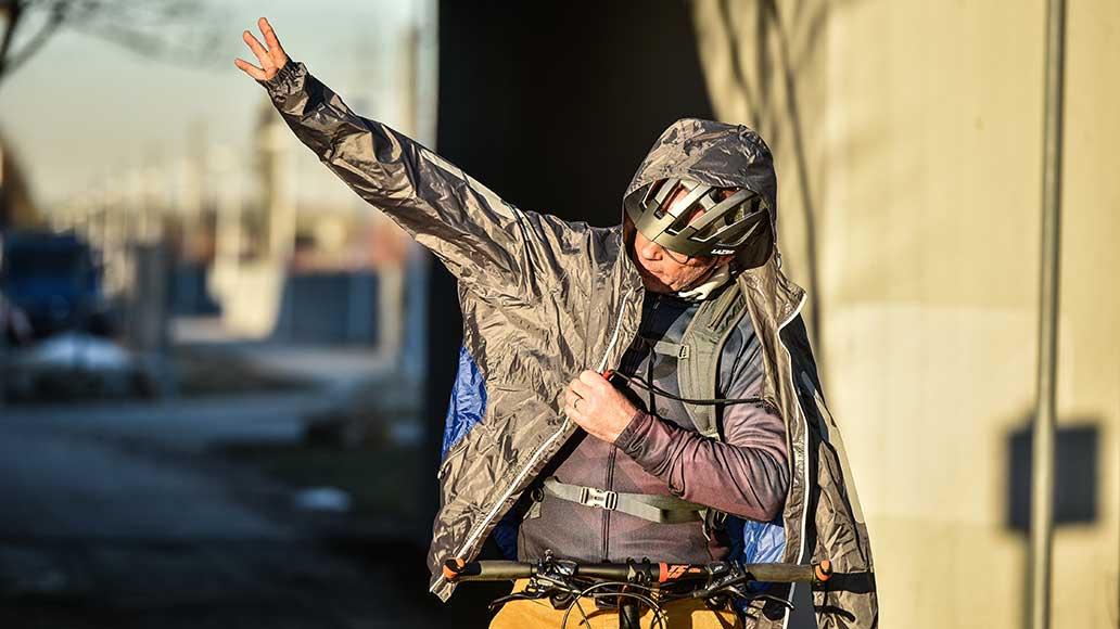 Ohne den Rucksack abzusetzen, kann die Jacke entfaltet und angezogen werden.