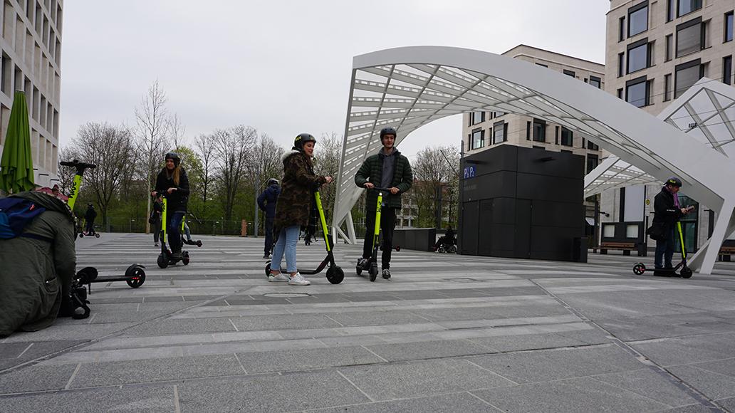 Großer (Straßen-)Bahnhof: An der Tram-Haltestelle Schwabinger Tor stechen die neongelben Scooter aus dem April-Grau heraus.