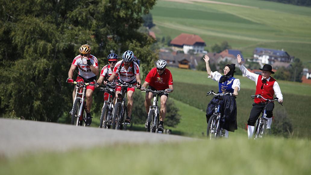 Trachten auf dem E-Bike oder Funktionskleidung auf dem Mountainbike. Der Autor fragt sich: Ist E-Biken eigentlich Sport?